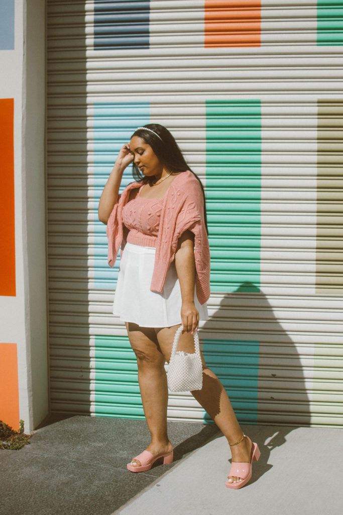 Valentine's Day Outfit Inspiration: Pink cable knit cardigan and bralet set from River Island, white pleated tennis skirt, Gucci Woman's rubber slide sandal